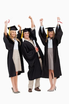 Three students in graduate robe raising their arms