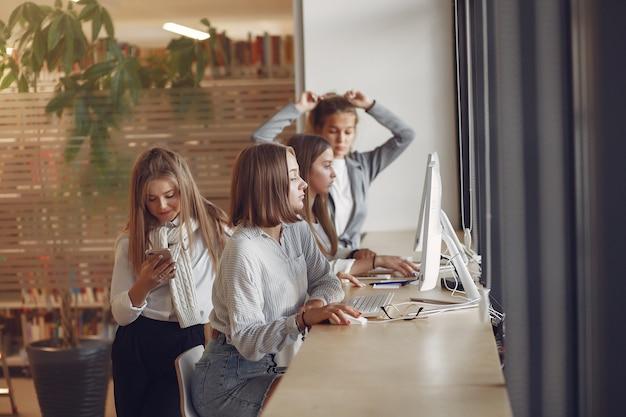 Трое студентов сидят за столом в классе