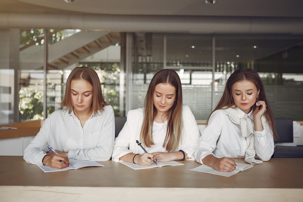 Three students sitting at the table in a class
