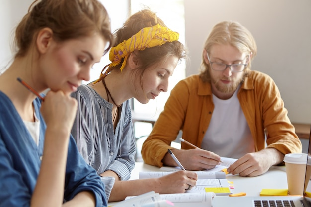 Tre studenti seduti insieme sul posto di lavoro, scrivendo con le matite e studiando letteratura scientifica, preparandosi per gli esami all'università. ragazzo barbuto e due femmine che lavorano al progetto