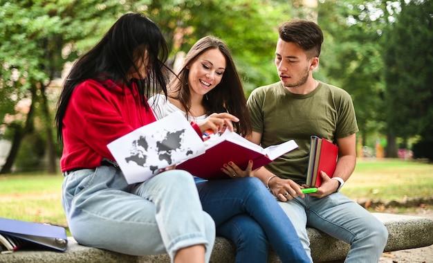 屋外のベンチに座って一緒に勉強している3人の学生