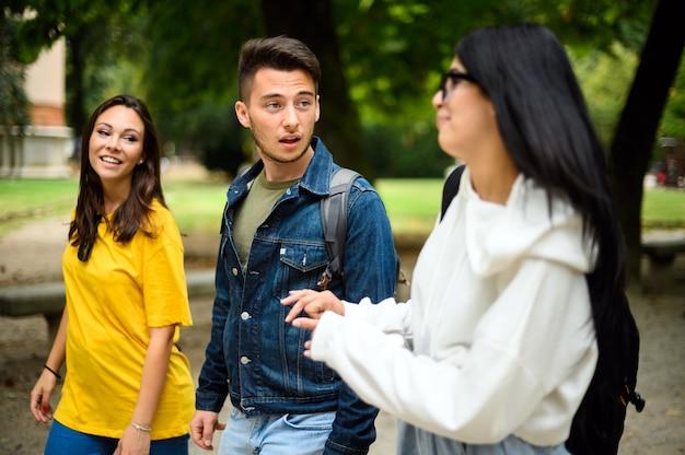 大学の中庭で屋外で話している3人の学生