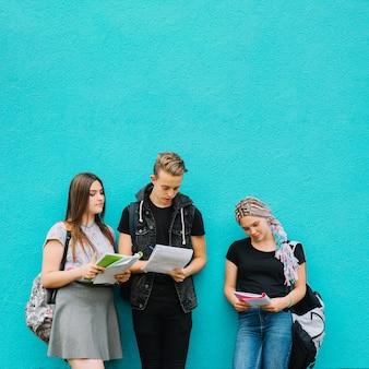 Tre studenti con libri su blu