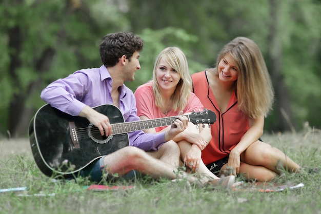 Three students with a guitar sitting on the grass in the city park.