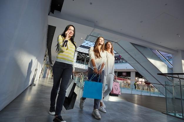 Три стильные девушки, одетые в красивую повседневную одежду, гуляют с множеством сумок для покупок по торговому центру