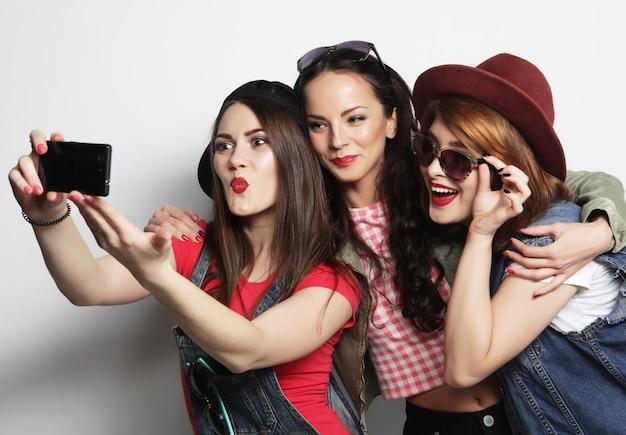 携帯電話で自分撮りをしている3人のスタイリッシュな流行に敏感な女の子の親友