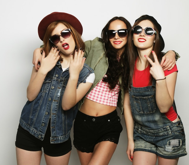 3人のスタイリッシュでセクシーなヒップスターの女の子の親友。一緒に立って楽しんでいます。カメラを見てください。灰色の背景の上。