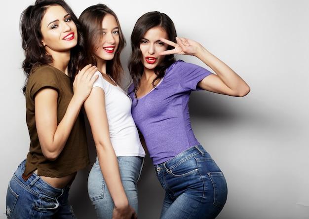 세 명의 세련된 섹시한 힙스터 소녀 가장 친한 친구입니다. 함께 서서 즐거운 시간을 보내고 있습니다. 회색 배경 위에.