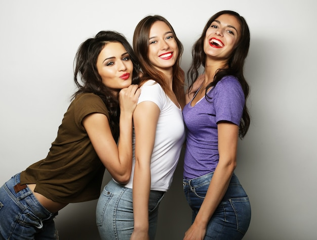 Три стильные сексуальные хипстерские девушки лучшие друзья. стоят вместе и веселятся. на сером фоне.