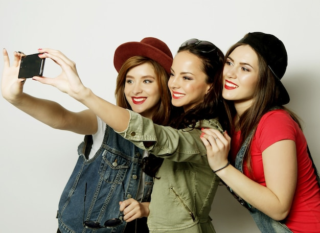 携帯電話で自分撮りをしている3人のスタイリッシュでセクシーなヒップスターの女の子の親友