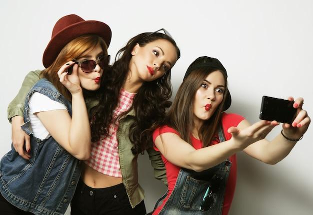 휴대 전화로 셀카를 찍는 세 명의 세련된 섹시한 힙스터 여자 가장 친한 친구