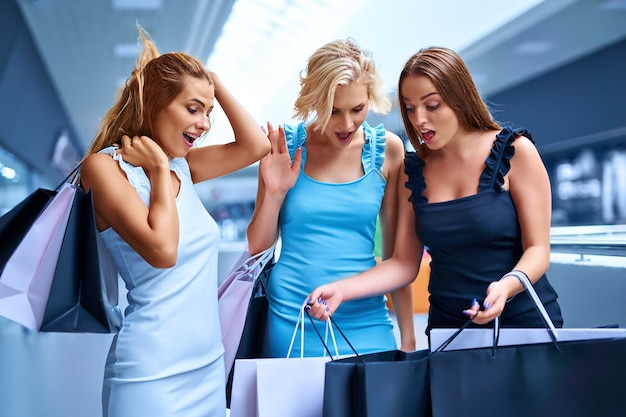Three stylish woman holding shopping bags after shopping sale consumerism black friday