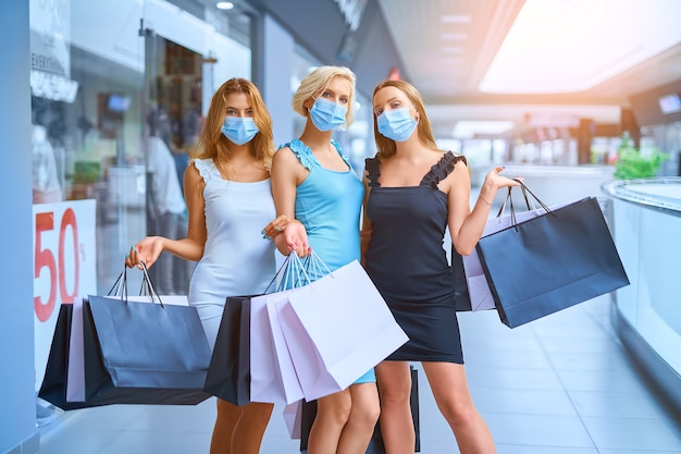Three stylish woman in protective medical mask holding shopping bags after shopping shopping in the ...