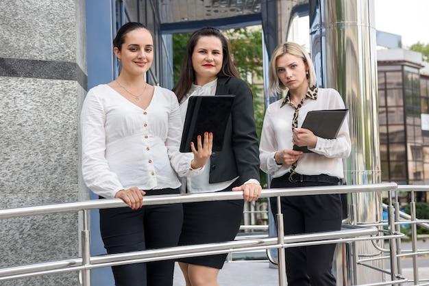 사무실 중앙 입구 앞에 서있는 세 명의 성공적인 비즈니스 여성