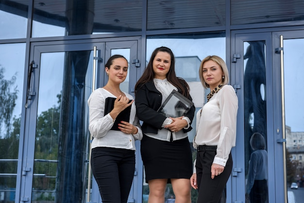 オフィスの中央入口の前に立っている3人の成功したビジネス女性