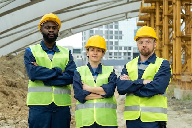 안전모와 제복을 입은 세 명의 성공적인 엔지니어 또는 건축업자