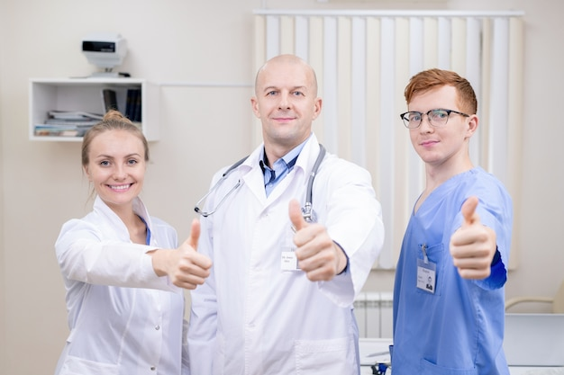 Three successful professionals in medical uniform showing thumbs up while looking at you in clinics