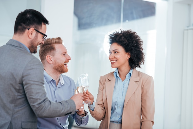 Three successful young business people toasting with drinks.