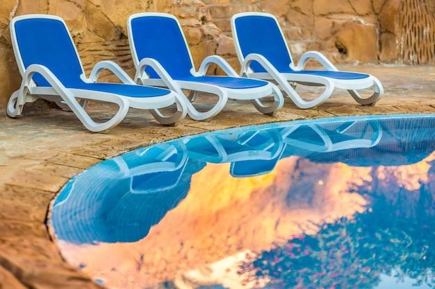 Три шезлонга отражаются в голубой воде бассейна