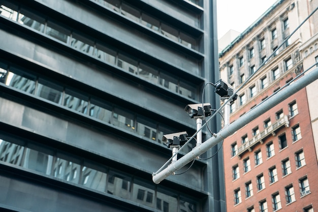 Three surveillance cameras on a street pole with large buildings in the background - close-up