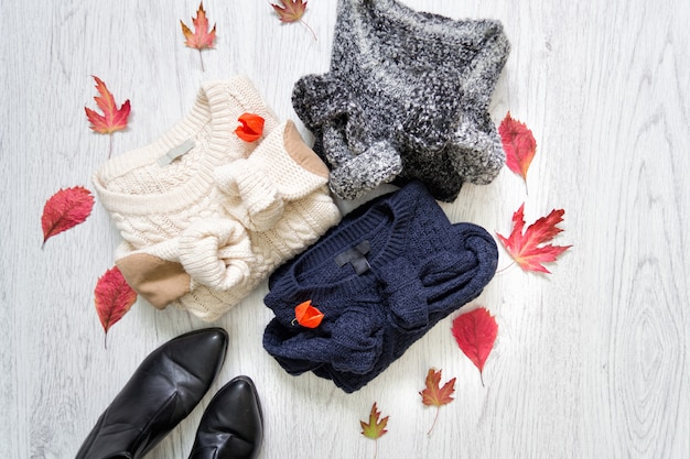 Three sweaters and black shoes with red leaves