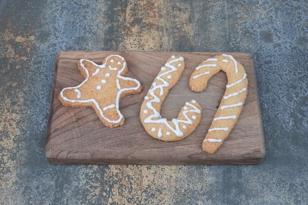 Tre dolci biscotti di natale sulla tavola di marmo.