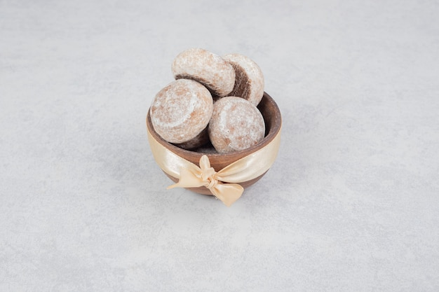 Tre biscotti dolci con fiocco dorato sulla ciotola di legno