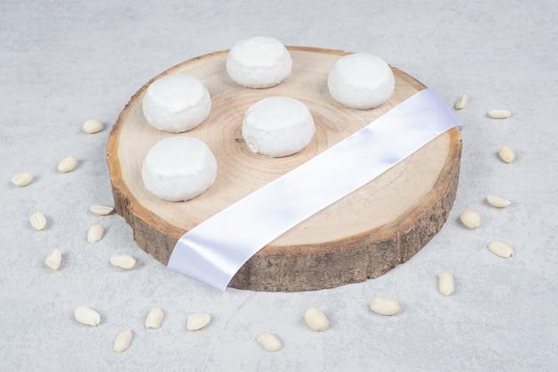 木の板に白いリボンが付いた3つの甘いクッキー。高品質の写真