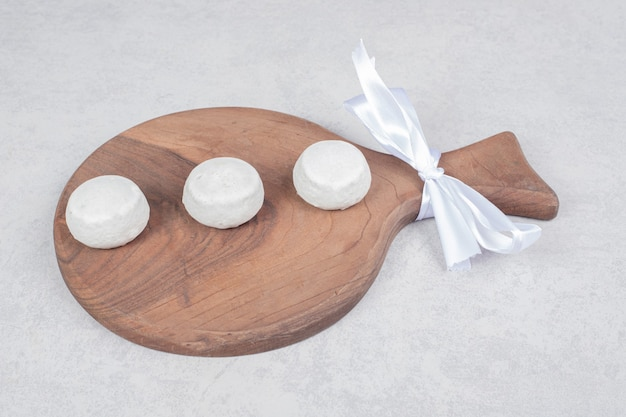 Three sweet cookies with white bow on wooden board. high quality photo