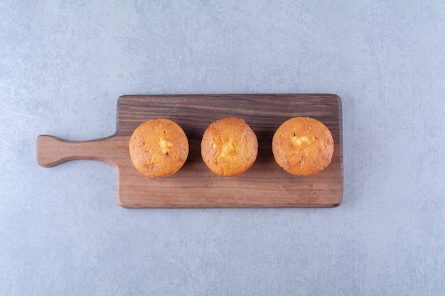 Три сладких вкусных кекса на деревянной разделочной доске.