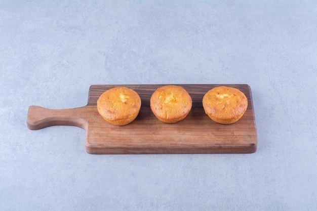 Три сладких вкусных кекса на деревянной разделочной доске