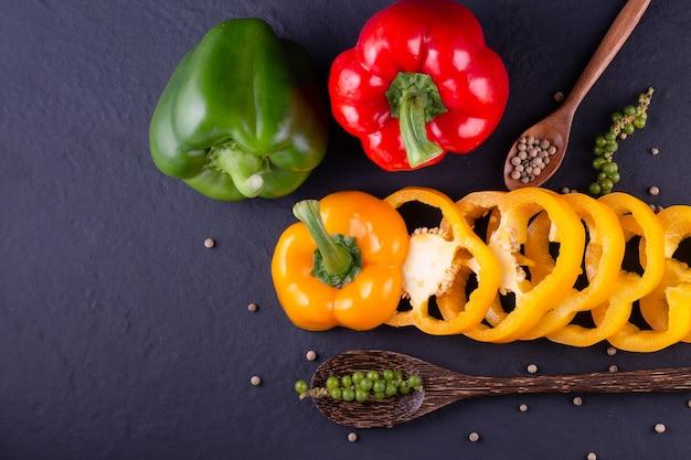 木製のテーブルに3つのピーマン、野菜サラダを調理