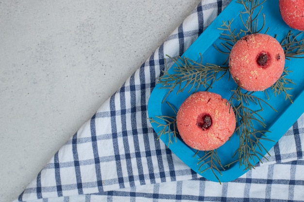 Three sweet pink round cookies on blue plate