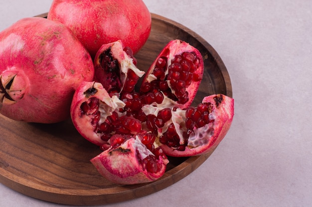 Three sweet pomegranate on wooden board on white.
