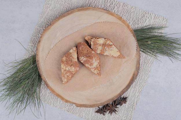 Три сладких ломтика пирога с звездчатым анисом на деревянной тарелке. фото высокого качества
