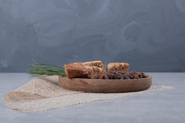 Три сладких кусочка пирога с звездчатым анисом на деревянной тарелке.
