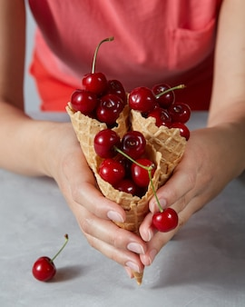 Three sweet waffle cones with ripe cherries holding girls hand on a gray background. summer concept of homemade desserts.