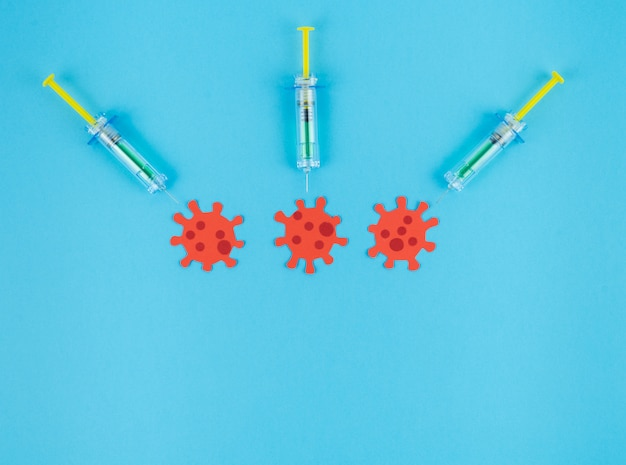 3つの赤いウイルスを刺す3つの注射器が紙から切り取られました。コンセプトcovid-19。
