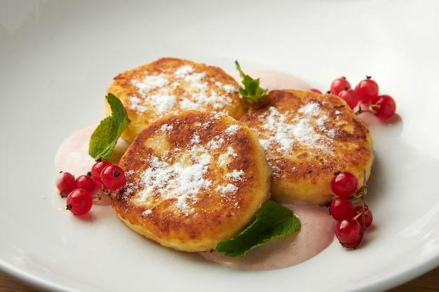 Три сырника на тарелке из красной смородины, посыпанной сахарной пудрой на тарелке