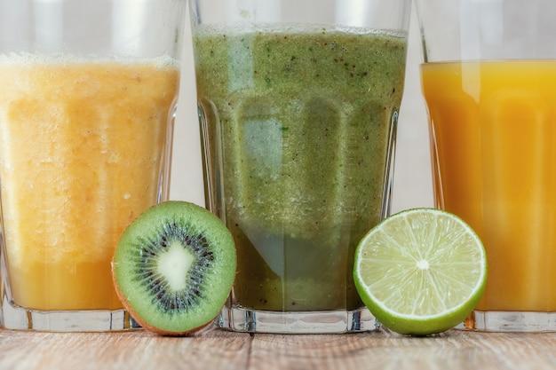木製のテーブルの上に果物に囲まれたキウイとほうれん草のスムージーが並んだ3つの背の高いガラス。