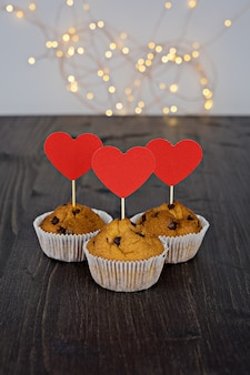 Three tasty chocolate muffins with big red hearts