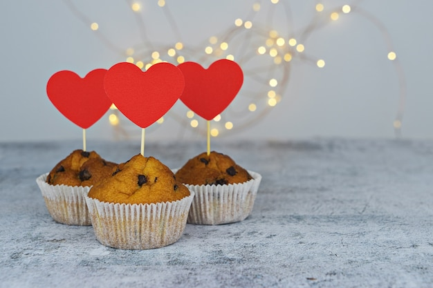 Three tasty cupcakes with big red hearts