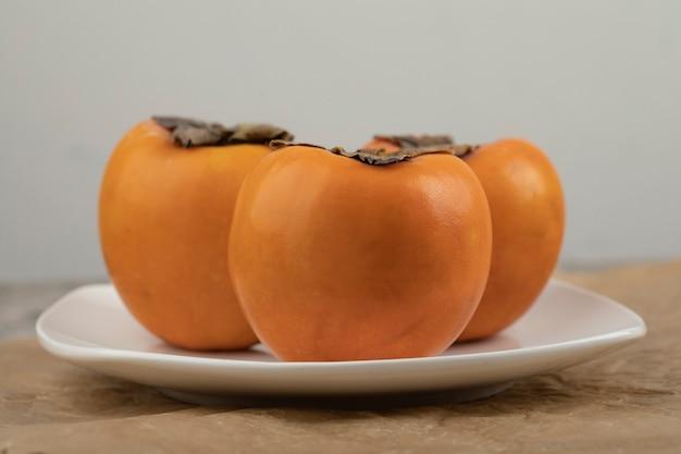 大理石の表面の白いプレートに3つのおいしい冬柿
