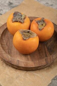 大理石の表面の木板に3つのおいしい冬柿