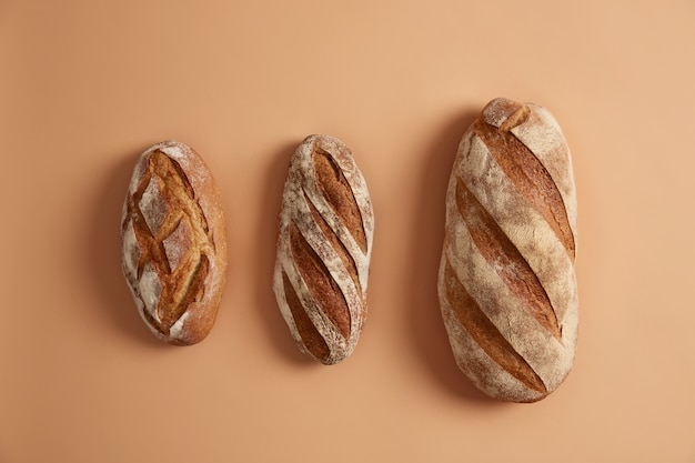 Three tasty loaves of bread arranged on beige background. gluten free homemade bakery products. organic freshly baked buckwheat white bread on leaven. innovative baking concept. overhead shot
