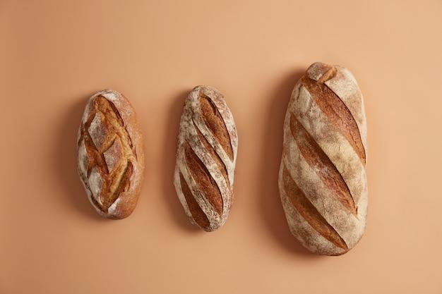 베이지 색 배경에 정렬 된 빵 세 가지 맛있는 덩어리. 글루텐이없는 홈 메이드 베이커리 제품. 누룩에 갓 구운 유기농 메밀 빵. 혁신적인 베이킹 개념. 오버 헤드 샷