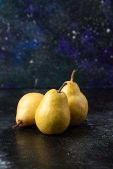 Tre gustose pere gialle disposte su una superficie nera.