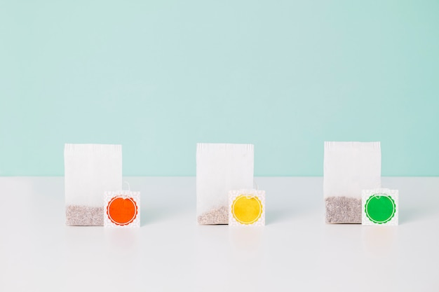 Three teabags with red, yellow and green label isolated