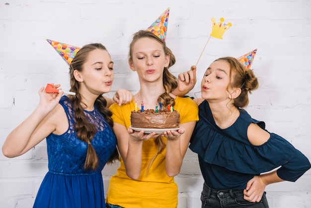 Three teenage female friends blowing candles on birthday cake