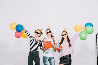Three teenage female friends holding wrapped gift boxes standing against the wall
